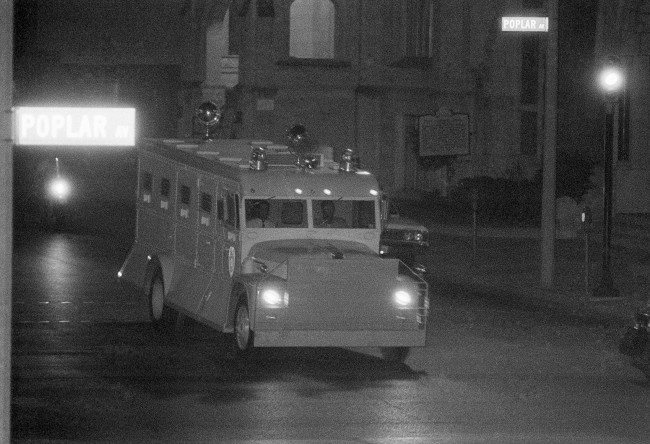 "Armored truck, borrowed for the occasion from Jackson, Mississippi, officials, delivers James Earl Ray to the Shelby County Jail in Memphis, Tennessee, July 18, 1968, before dawn, following his flight from London. Inside the van, Ray was wearing ""safety equipment"" of material similar to the military flak vest."
