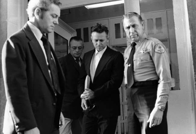 James Earl Ray leaves the Shelby County Jail escorted by US marshals and sheriff's deputies enroute to the federal court in Memphis, Tennessee, Oct. 22, 1974, to hear claims that Ray was pressured into pleading guilty to the slaying of Dr. Martin Luther King.