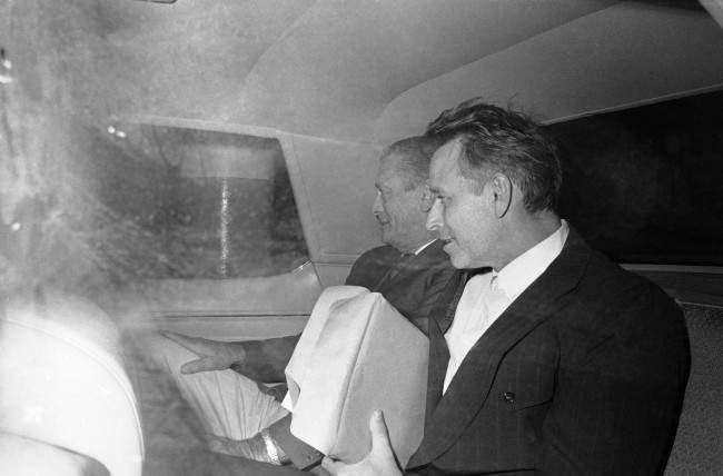 James Earl Ray, right, almost smiles as he gazes at newsmen outside the car taking him from federal court in Memphis, Tennessee on Oct. 23, 1974, back to his jail cell. Ray, who usually walks expressionless with his head down, is claiming in court that he was pressured into pleading guilty in the slaying of Dr. Martin Luther King. A US marshal is at left.