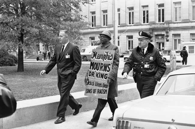 A plainclothes detective and a uniformed Shelby County Deputy sheriff usher away from the Shelby County Jail a picket who attempted to walk the sidewalk around the courthouse where James Earl Ray was scheduled to go on trial in Memphis, Tennessee on Nov. 12, 1968. Ray is accused of the murder of Dr. Martin Luther King.