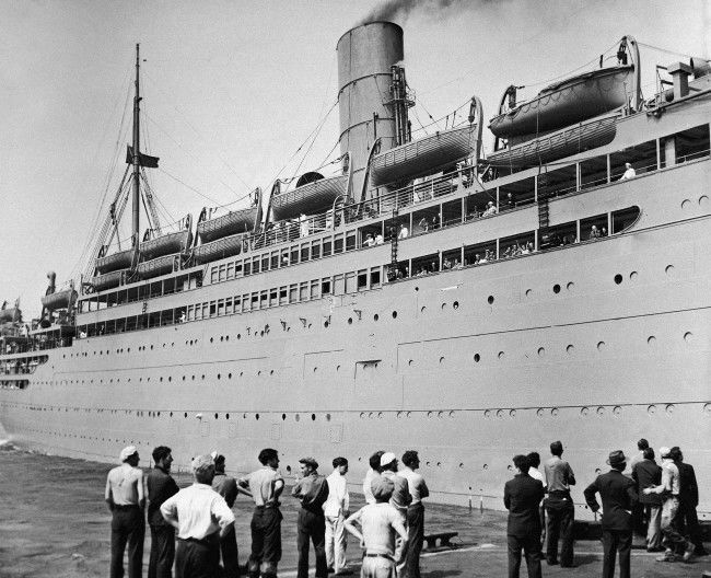 "Painted Gray, in order of camouflage it from the ""enemy,"" the liner Franconia slipped out of its pier on Sept. 2, 1939, for a voyage back to its home port in England. Formerly painted a spotless white for cruise service, Franconia was hastily repainted and portions of its deck reinforced by sandbags for its drip from New York to England throughout waters which may be extremely dangerous before the voyage is completed."