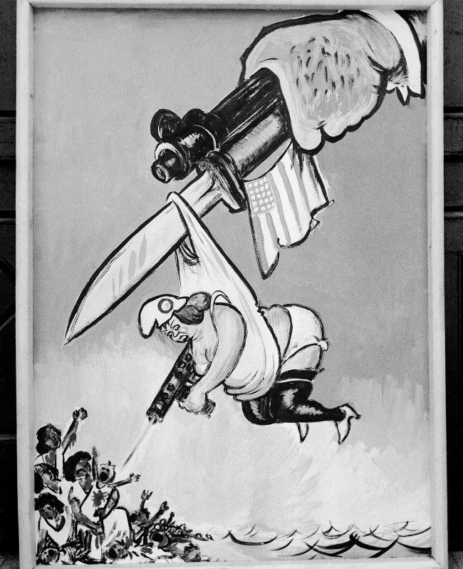 An anti-French cartoon, showing a fat Marianne killing Algerian women and children while held up by a U.S. - marked bayonet in Cairo, Egypt, March 30, 1958. (AP Photo/A. Maseraff)