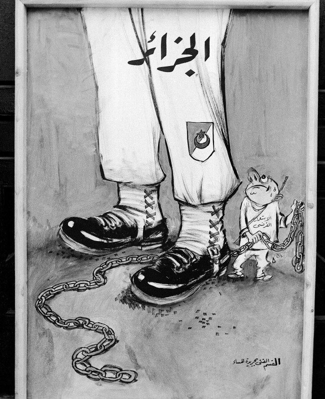"Cartoon-banner shows the strong legs of an Algerian nationalist soldier who seems unworried about ""French Imperialism's"" attempt to chain him in Cairo, Egypt shown March 30, 1958."