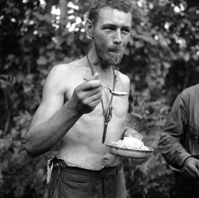 This unidentified U.S. soldier eats his first hot meal after 11 days in the jungles of New Guinea on Dec. 26, 1942, where he not only contended with Japanese who surrounded his group the last two days, but fought insects which raised welts on his mid-section.
