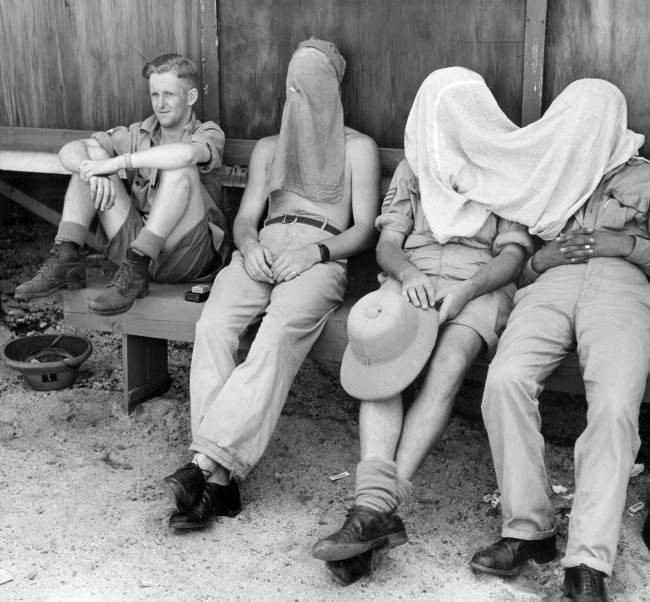 Protected by veils against the onslaught of the annoying and germ bearing-mosquito, three New Zealanders relax in the shade on Espiritu Santo on April 18, 1944, where they are receiving instruction in the operation of U.S. Navy planes. A comrade, scorning the netting, lets the mosquitoes 'fire away.