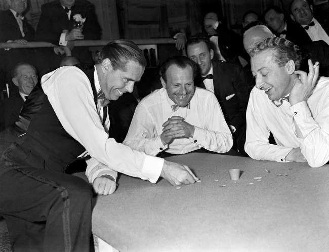 Tiddlywinks - World Championship Tiddlywinks Match - Cambridge University v The Empress Club - Empress Club, London The Earl of Kimberley, left, squidges for the pot, watched by Terry Thomas (centre) and Kevin McClory.