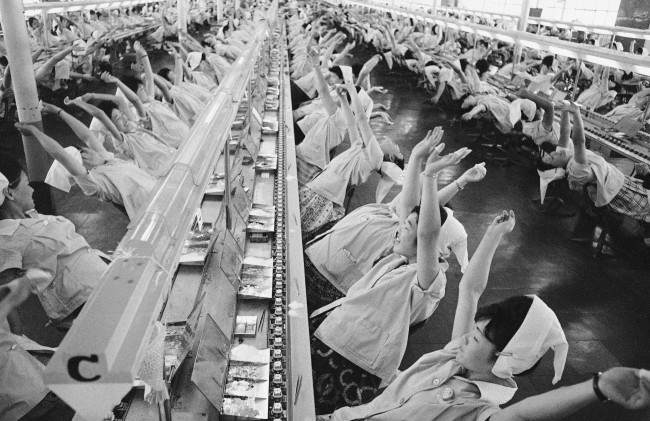"""Stop working, take a deep breath, one, two, three, four."" says a loud speaker. Then, you'll see such a ""mass yawning"" at the factory of Mitsumi Electric Company on the outskirts of Tokyo, Japan, shown May 7, 1963. Workers along assembly lines at the transistor radio parts maker take a brief break every hour in this unusual way. This was helped promote the company''s productivity, according to the company officials. (AP Photo)"