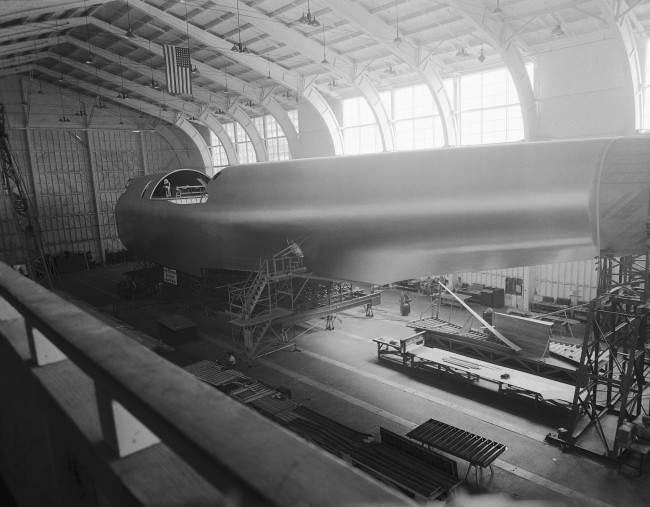This is the hull of the Hughes Hercules, called by its builders, the Hughes Aircraft company, the largest plane in the world under construction at Culver City, California on July 16, 1945. The hull is 220 feet long, 30 feet high and 25 feet wide, while the wing is 320 feet from tip to tip.