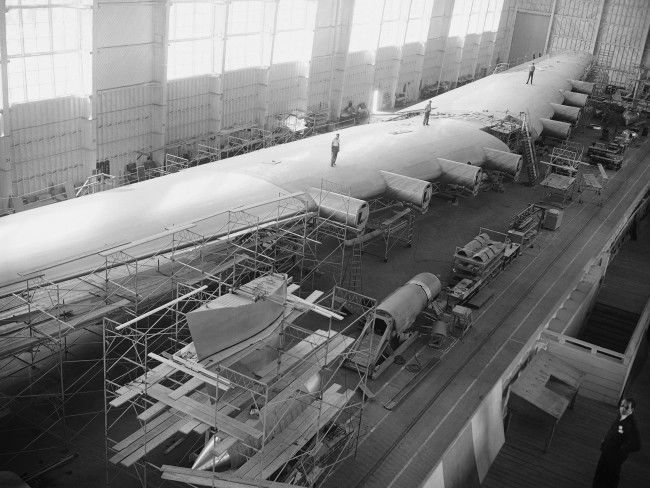 This is the wing of the Hughes Hercules, called by its builders the biggest plane in the world, nearing completion in the Hughes Aircraft Company plant in Culver City, California on July 16, 1945. The wing is 320 feet from tip to tip and 13 feet thick at the hull.