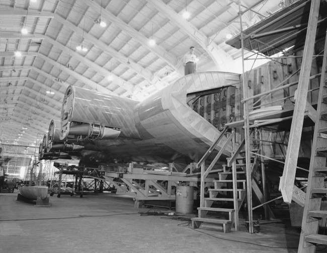 The Hughes Hercules nearing completion in Culver City, California on July 16, 1945. Thirteen feet thick at the center, this is a portion of the wing which its designers say will bear into the air a seaplane weighing more than 200 tons. Four of the engine mounts are shown in the background.