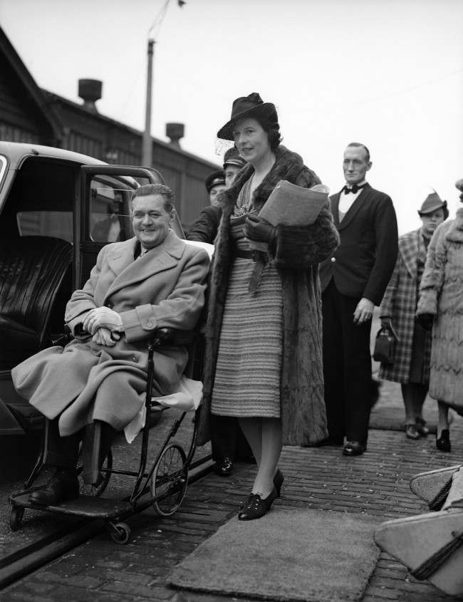 Derek McCulloch, Uncle Mac of the B.B.C., sailed on a cruise to Portugal to recover from his fortieth operation, the amputation of a leg. Derek McCulloch in his invalid chair with his wife,Eileen, at Southampton, England, on Feb. 17, 1939, before embarking in the liner Asturias. (AP Photo) Date: 17/02/1939