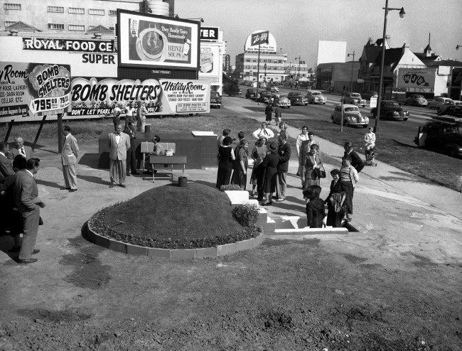 Two styles of bomb shelters are for sale at Bomb Shelter Mart, Wilshire Blvd., Los Angeles, Calif., shown March 23, 1951. It is typical of such markets which have sprung up in and around Los Angeles. Crowds stop by every day to inspect the shelter, a small circular one (foreground) and a larger one which can be furnished with a stove, radio and other equipment. Both can be used as storage areas. With Federal Housing Authority financing for home owners, they are expected to sell for $795 each. The shelters were built by the U.S. Bomb Shelter Company of Los Angeles.