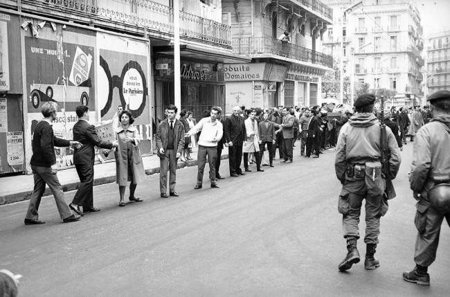 Long line of Europeans pass supplies by hand along an Algiers street, with the supplies eventually going to inhabitants of besieged Bab-el-Oued sector, March 25, 1962. The rightist stronghold has been encircled by French government troops on orders from President de Gaulle to smash the European secret army revolt.