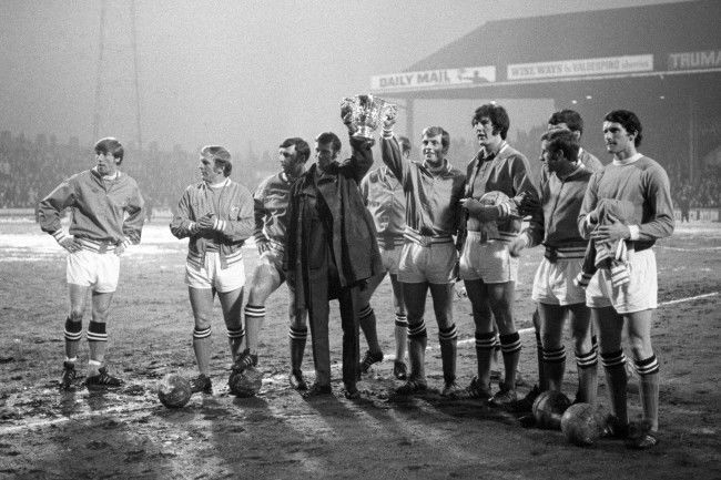 Shouts of 'We are the Champions' ring out as the Manchester City team show off the League Cup before the match. Holding it is captain Tony Book (dressed in a suit as he was not playing tonight) and Alan Oakes. (l-r) Colin Bell, Francis Lee, Glyn Pardoe, Tony Book, Joe Corrigan, Frank Carrodus and Mike Doyle. Archive-PA144656-2 Date: 11/03/1970