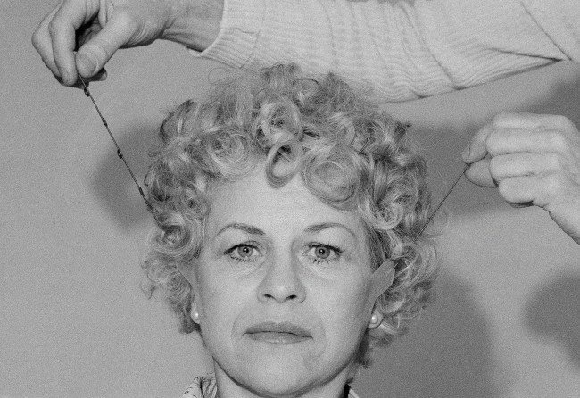 "Joanne Viggiano is the model for a temporary face lift by Mark Traynor at his studios in New York on Friday, March 11, 1977. The ""lift"" a combination of tape and elastic cord is placed at three areas of the face - the upper forehead, in front of the ears and at the neck."