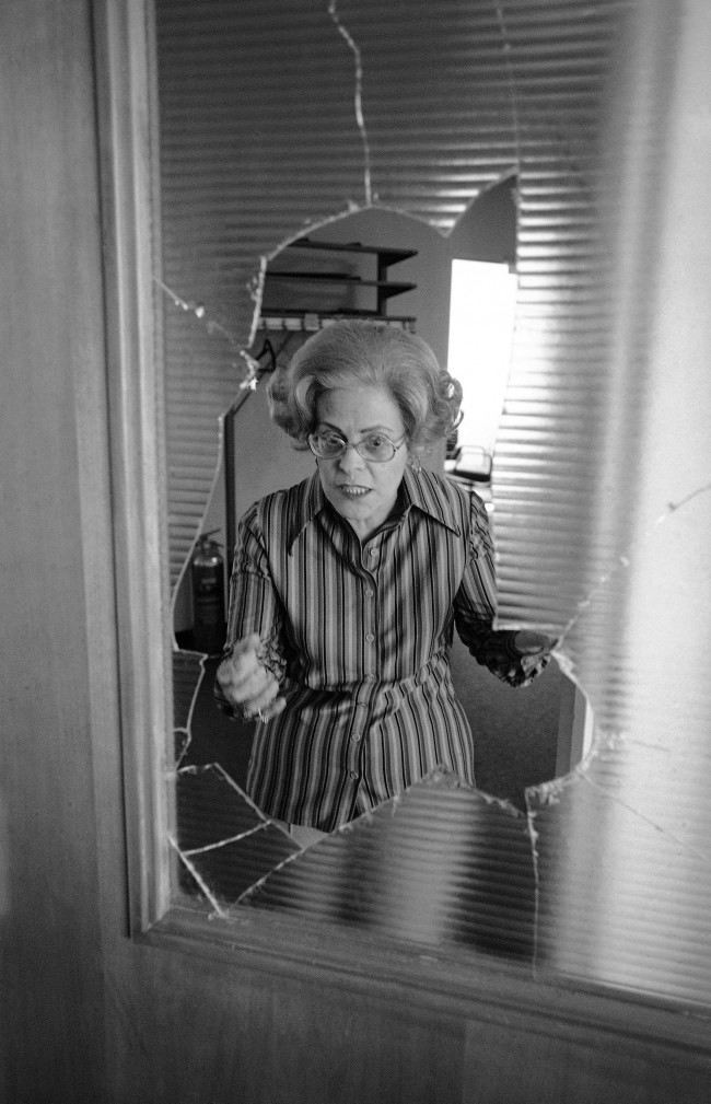 Rae Ehrlich is framed by a broken glass partition, at B'nai B'rith headquarters in Washington on Sunday, March 14, 1977 as she explains how gunmen broke the glass with a rifle butt and took her and others hostage. Over a hundred captives were held for 38 hours.
