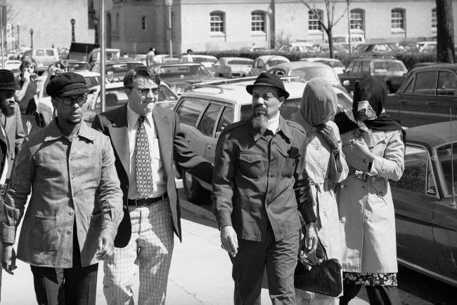 Hamaas Abdul Khaalis, Hanafi Muslim leader, arrives at district court on Thursday, March 31, 1977 in Washington along with his two veiled wives where a preliminary hearing was to be held on charges stemming from the siege of three buildings in Washington along with hostages.