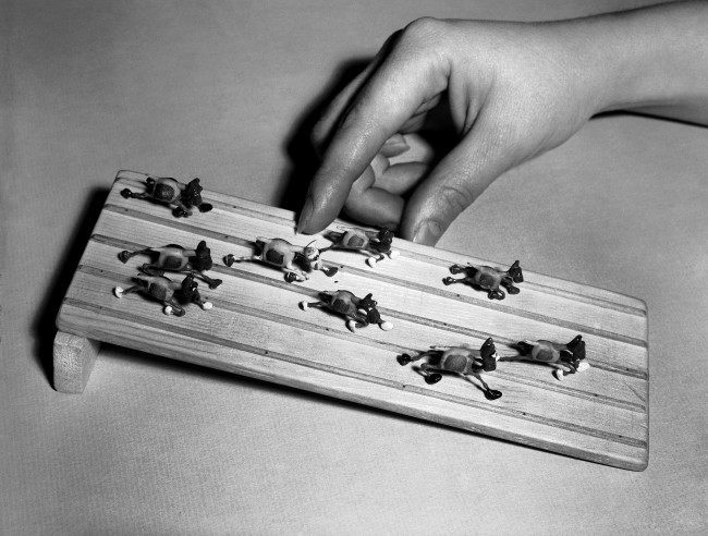 "These ""jumping horses"", invented by a retired accountant of Moline, Ill., have a center section composed of a Mexican jumping bean encased in a hand-carved horse frame. It's fun trying to pick a winner as the nerve center activated by the bean causes the horses to move down the track, shown at the Gadget of the Month club in Los Angeles, March 31, 1951."
