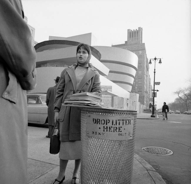 Resting her books on a New York waste basket industrial design student Christl Wilhelm says the building behind her has no warmth and no spirit, March 31, 1959. She''ll get a lot of argument from devotees of architect Frank Lloyd Wright, whose works always seem to stir arguments. Wright designed the vat-shaped structure on upper Fifth Avenue. It is the Solomon R. Guggenheim Museum.