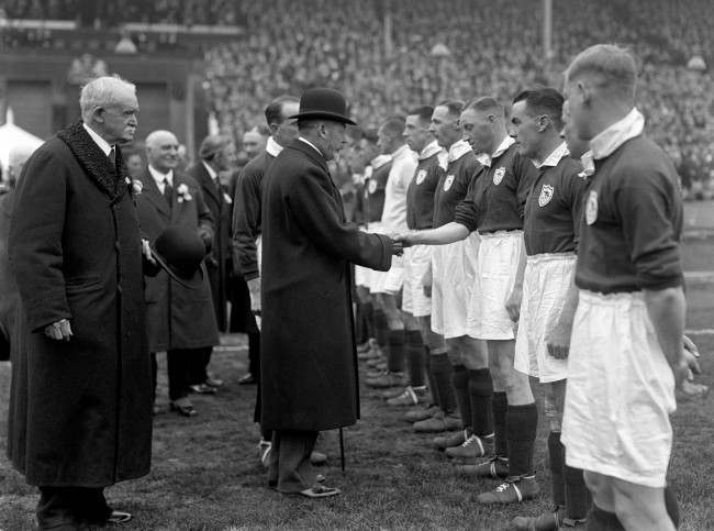 King George V attends the cup final at Wembley in 1930. He shakes hands with the Arsenal team before the start of the match.