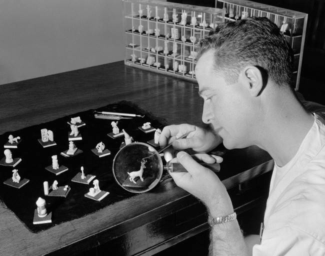 With the aid of a magnifying glass, Doyle J. Davis, freshman dental student at the University of Southern California, carves a miniature deer, April 7, 1955. It's class work, not a hobby. Because hand skill is important to a dentist, Dr. William P. Harrison, who conducts a dental anatomy class at the university, originated 25 years ago a creative wax-carving test to determine the manual dexterity of his freshman students. His campus office contains some 3,000 miniature objects which the students carved from tiny cylindrical pieces of hard caruba wax only 1-inch high and three-quarter of an inch wide.