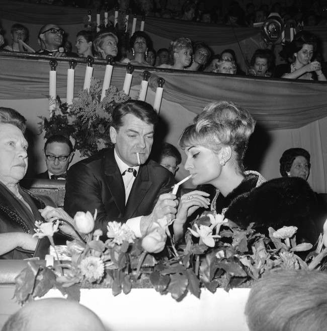 French actor Jean Marais, center, lights up the cigarette of Francoise Garbine at the Cirque d'Hiver (Winter Circus) on March 8, 1963 in Paris, France. Sitting at left is his mother.