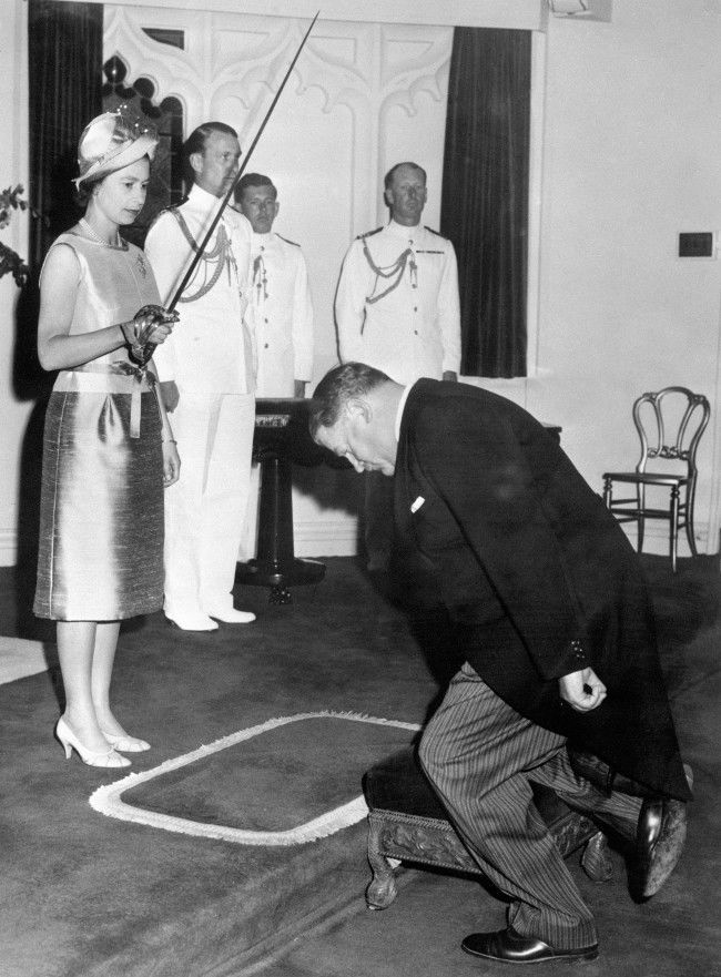 Queen Elizabeth II bestows the accolade of knighthood on the kneeling Sir Roy McCaughey of New South Wales, at Government House, Sydney.