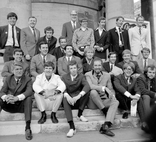 """Mr Robin Scott, Controller, Light Programme, who heads the BBC's new Radio 1 (Pop) and Radio 2 (Light) radio network, pictured (centre, background) at Broadcasting House, Portland Place with disc jockeys who will be in the spin of things on Radio 1, many of them were formerly with """"pirate"""" radio stations. Left to right: Back row - Tony Blackburn, Jimmy Young, Kenny Everett, Duncan Johnson, David Rider, Dave Cash, Pete Brady and David Symonds. Middle row - Bob Holness, Terry Wogan, Barry Alldis, Mike Lennox, Keith Skues, Chris Denning and Johnny Moran. Front row - Pete Murray, Ed Stewart, Pete Drummond, Mike Raven, Mike A'Hern and John Peel. Date: 04/09/1967"""