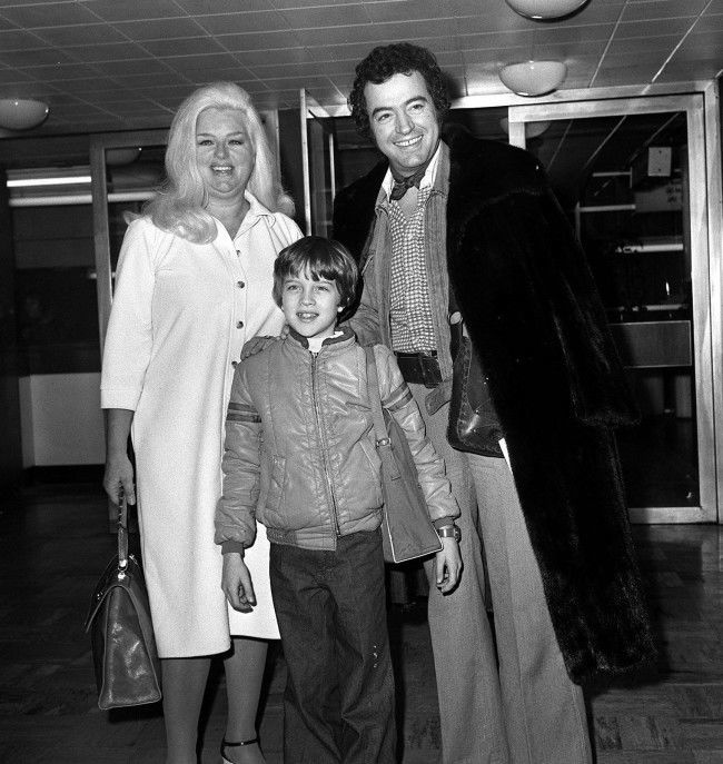 Off to Hollywood, California from London's Heathrow airport today, are actress Diana Dors, her husband, actor Alan Lake, and nine year old son Jason. Alan who feels the cold, wears one of Diana's own Christmas presents - a full length mink coat. In America, Miss Dors will visit her grown up sons and appear on TV chat shows. Ref #: PA.1244666 Date: 28/12/1978