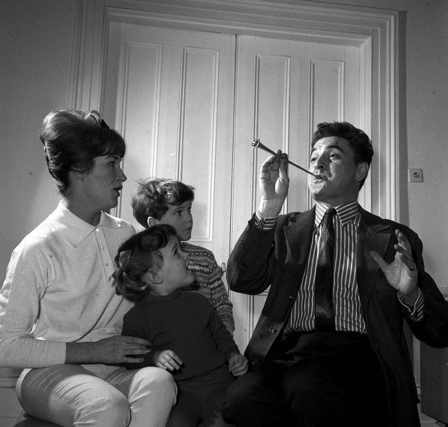 "Scripwriter and comedian Bob Monkhouse with his family, wife Elizabeth, son Simon (centre behind), and adopted daughter Abigail, in their St John's Wood home in London. * 11/05/01 The son of Bob Monkhouse has been found dead in Thailand, a Foreign Office spokesman said. The body of Simon Monkhouse, 46, was found in Bangkok on April 14 but details of his death were only released today, a spokesman said. Mr Monkhouse, from Lambeth, south London, was holidaying alone in Bangkok when his body was found in a hotel, the Sun said. 12/5/01: Monkhouse's ex-wife Elizabeth, Saturday May 12, 2001 told for the first time how she was struggling to cope with the death of her son Simon in Thailand. She said she felt ""utterly bereft"" to lose a second child after the couple's son Gary died nine years ago and revealed that the last time she heard from Simon, 46, he was""healthy, happy and having the holiday of a lifetime"". Meanwhile 72-year-old Monkhouse, who admitted falling out with his son years ago, said he was heartbroken that he would never get the chance to have a reconciliation with him. *29/12/03: Veteran British comedian and television host Bob Monkhouse who died, aged 75, after losing a lengthy battle with prostate cancer.  Ref #: PA.1253487  Date: 23/02/1962"