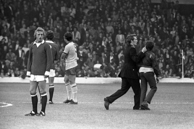 Soccer - League Division One - Manchester United v Arsenal - Anfield, Liverpool Manchester United's Denis Law waits patiently as a Policeman grabs a youth by his ear and leads him off the pitch. Manchester United were banned from playing at home for the first two games of the season following hooliganism at Old Trafford the previous season. Archive-PA153218-2a Ref #: PA.12586519 Date: 20/08/1971