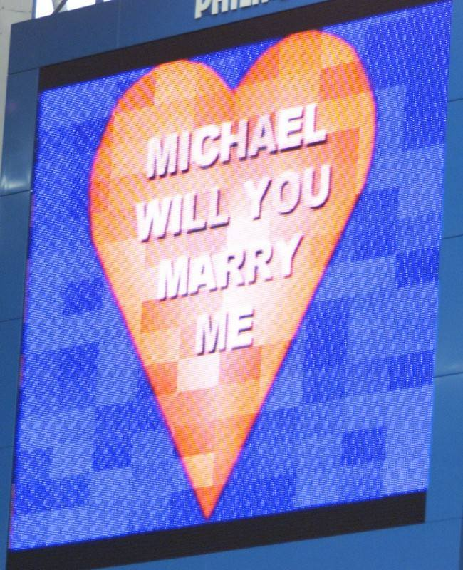 Valentine's Day came early for a Chelsea-mad football fan whose girlfriend marked his first ever visit to Stamford Bridge by proposing to him in front of 30,000 fans. Amanda Kirk, 22, popped the question on the club's giant scoreboard. * 30-year-old Michael Evans said Yes as soon as he had got over the shock. For design engineer Mr Evans it was a triply special day. It was his first ever match at the home of the Blues, despite being a lifelong fan.Then came Amanda's half time proposal. And to top it all, his beloved team ran out 3-1 winners over London rivals Wimbledon. Mr Evans and Miss Kirk travelled to London with his daughter Leanne from their parents' homes in South Wales.