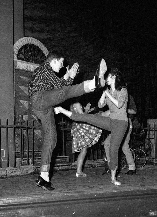 "Billy Boyle and Audrey Carr dancing a vigorous Twist on the stage of the Garrick Theatre in London during a rehearsal of ""The Scatterin'"" an Irish play by James McKenna, opening at the Theatre Royal in Stratford. Billy Boyle, an 18-year old variety star is billed in Ireland as ""Dublin's teenage idol"". Boyle played a minor role so well in the original production at the 1960 Dublin Theatre Festival, that he was chosen by director Alan Simpson for a leading part in the London production. The play's story centres on four Dublin boys, is told in dialogue and in over 20 musical numbers ranging from traditional ballads though rock 'n' roll, to the Twist."