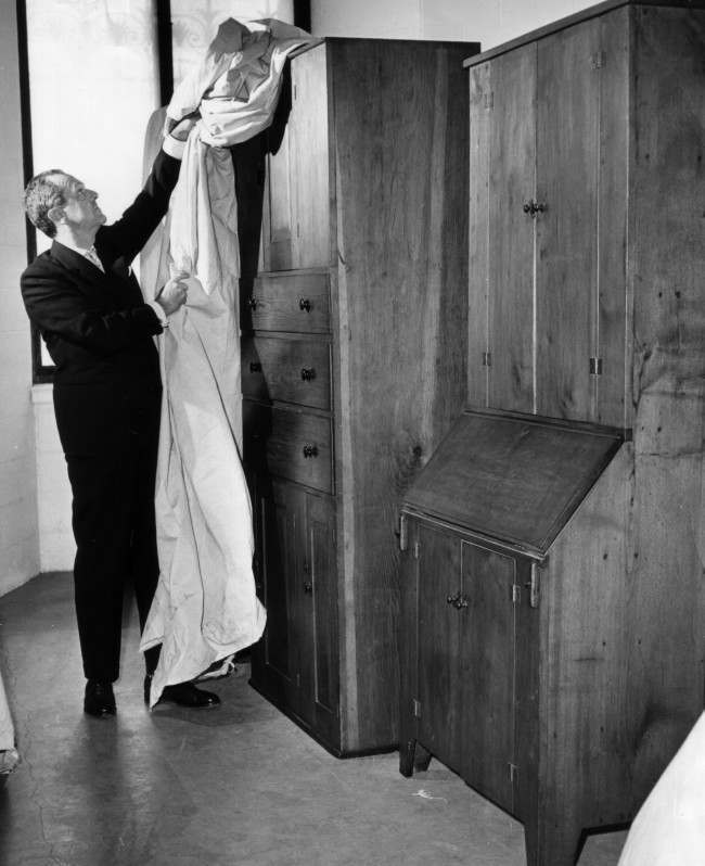 Henry McIlhenny, curator of decorative arts at the Philadelphia Museum of Art in Philadelphia, March 29, 1962, uncovers chest of drawers and slant-top desk made by members of the early-American religious sect known as the Shakers. The museum is preparing a month-long exhibit starting April 19 of what they believe will be the largest collection of Shaker crafts over assembled. The Shaker materials will be exhibited in six special galleries now under construction duplicating the plain residences of the sect.
