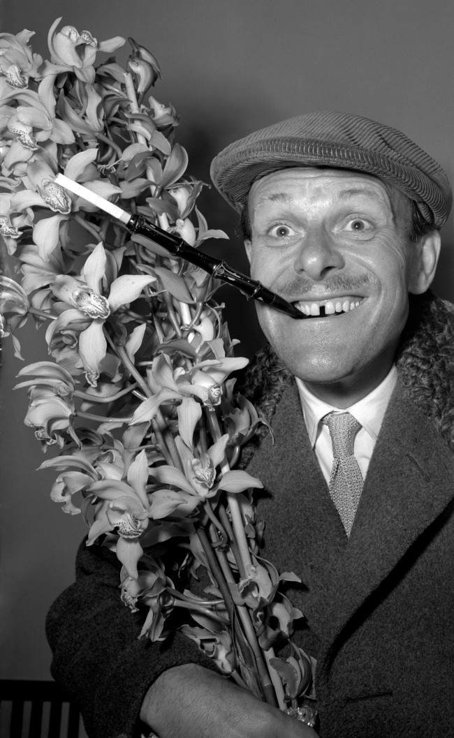 : TV's elegant comedian Terry-Thomas, who exhibits a distinctive sartorial style, returns from a holiday in Madeira sporting a cap and extended cigarette holder. He carries a bush of orchids for his wife. He is pictured at Southampton. Date: 25/03/1952