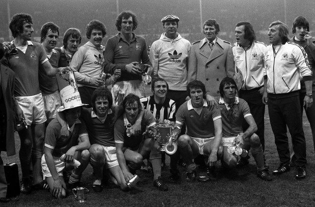 Happy manchester City players and officials with the trophy after their 2-1 victory over Newcastle United in the football League Cup Final at Wembley. From left: Back row - Tommy Booth, Joe Royle, goal scorer Peter Barnes, substitute Ken Clements, goalkeeper Joe Corrigan, and manager Tony Book (wearing overcoat) flanked by City trainers. In front: Gerard Keegan (hat), Willie Donachie, Asa Hartford, goal scorer Dennis Tueart, captain Mike Doyle and Dave Watson.