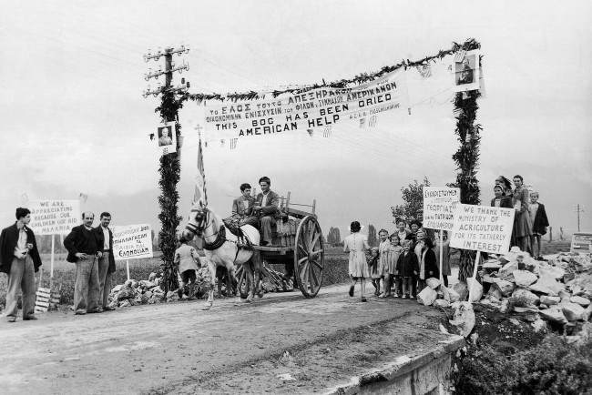 This arch outside Anthele, Greece on Nov. 14, 1946, is decorated with slogans thanking America for her help in farm development and for clearing malaria breeding grounds. A picture of President Harry Truman is on the post left.