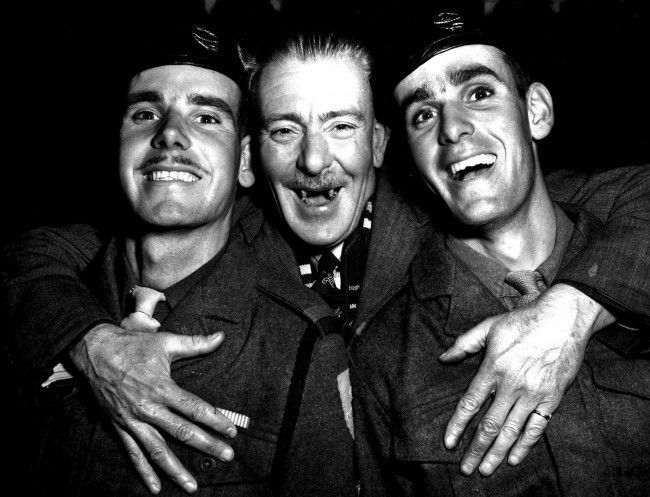 A happy reunion at Southampton as the trooper Empire Orwell returns with 750 British servicemen from Korea, Clasping his twin sons (21) is ex-CSM George Wood. His sons are Donald (left) and Ronald, members of the 7th Royal Tank Regiment.  Date: 09/11/1951