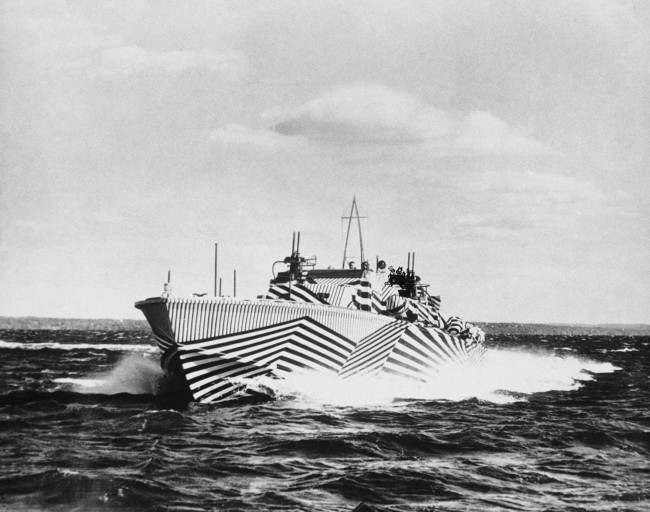 Newly camouflage to deceive enemy gunners, this American PT boat carries the heaviest armament of any boat in the navy for her size. Eighty feet in length, she carries four torpedoes, depth charges and rapid fire guns, during a trial, on Dec. 9, 1943.