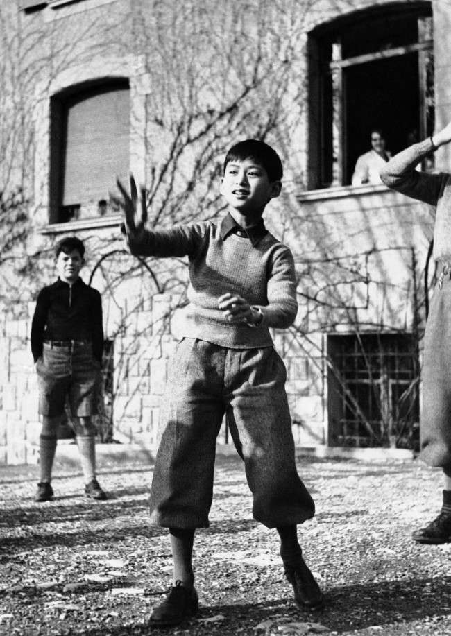 Like any other youngster, Prince Ananda, appointed to succeed his uncle, King Prajadhipok, as ruler of Thailand enjoys games as this exclusive picture of him at play outside the preparatory school he attends at Lausanne, Switzerland March 18, 1935.
