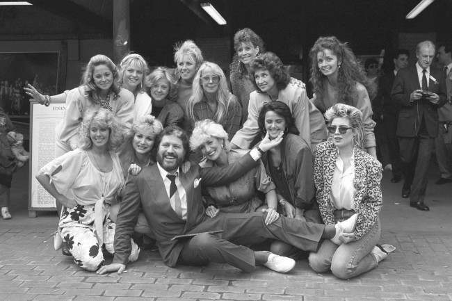 DJ Dave Lee Travis is surrounded by some of the women who appear in his photography book A Bit of a Star. Back Row L-R: Unidentified, Janet Ellis, Rosalind Ayre, Sarah Greene,Georgina Hale, Diane Keen, Jan Leeming, Cherry Gillespie. Front Row L-R: Jane Warner, Debbie Arnold, Dave Lee Travis, Faith Brown, Unidentified, Kim Wilde. Date: 27/05/1986