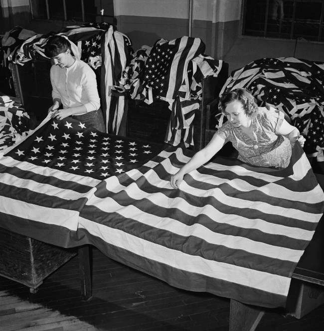 The new 49-star American flag is rolling off the assembly lines in ever increasing numbers and the Dettra plant, one of the largest, with a force of 240, is at work filling orders at Oaks, Penn., March 2, 1959. Judy Buse, left, and Mamie Myers check a completed flag for loose threads and other possible defects before shipment.