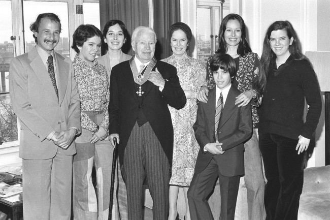 Sir Charlie Chaplin is back in his suite at the Savoy Hotel, after being knighted at the Palace, with his family. Behind him (l-r) His son-in-law Nick Sistovaris, daughters Annie and Josephine, wife Oona, son Christopher and daughters Geraldine and Jane. LUKEOTDI: Charlie Chaplin, the legend of silent film, became Sir Charles after a ceremony at Buckingham Palace. Chaplin starred in pictures such as The Kid and The Great Dictator, and was knighted in the New Year's Honours List.  Date: 04/03/1975
