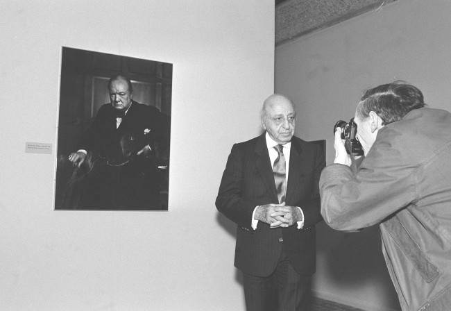 Facing the other side of the camera for a change, celebrated portrait photographer Yousuf Karsh is captured on film next to his famous large image of Sir Winston Churchill, taken in 1941, during the preview of his 80th birthday exhibition at London's Barbican Art Gallery. Date: 24/02/1988