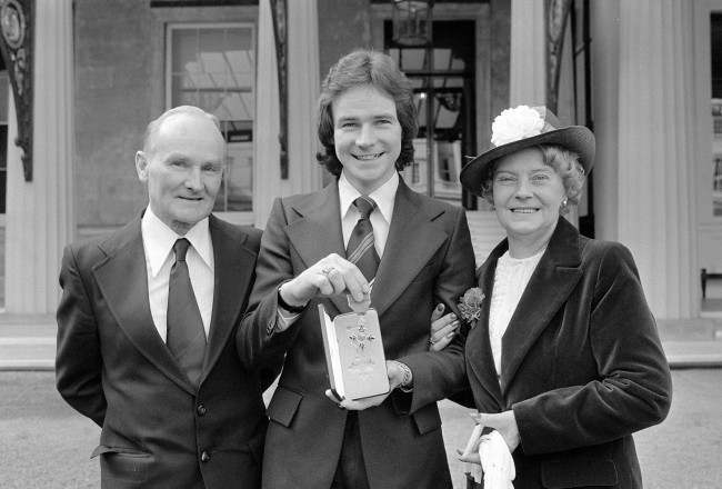 A proud moment for Britain's world motorcycling champion Barry Sheene as with his parents, Frank and Iris, he shows the insignia of MBE which he received from the Queen at an Investiture a Buckingaham Palace.