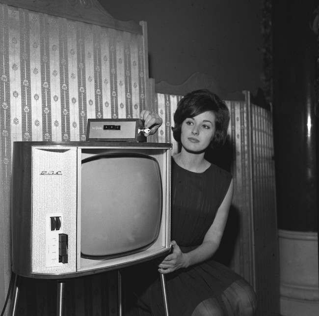 Diana Stones, 20, turns the key prior to selecting the desired channel on a TV set equipped with the new Marconi PayVision system in a London demonstration. The unit, a small box no larger than the average book, plugs into the aerial socket of any standard TV set and push-buttons select various PayVision channels. It costs only 5 to instal and average cost of programmes is 2/6d, with some public service and educational prgrammes free of charge. A central billing exchange automatically registers all programmes viewed. PayVision uses a closed circuit distribution system to bring three new TV channels into the home. The unit can be used with existing sets and does not affect present programme reception.