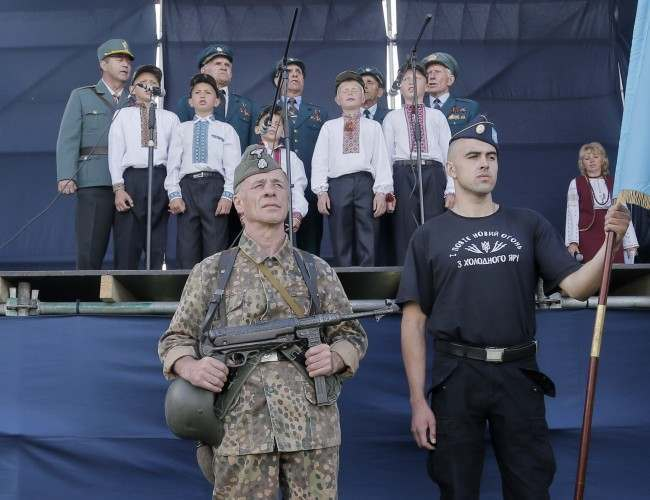 Two Ukrainians, one of them dressed in the SS Galychyna Division uniform, stand in guard of honor as children and SS Galychyna Division veterans sing during commemoration events in front of a monument to SS Galyhyna Division near the village of Yaseniv in western Ukraine on Sunday, July 21, 2013. Western Ukraine marks the 70th anniversary of creation of the SS Galychyna Division (the 14th Waffen Grenadier Division of the SS, 1st Ukrainian), a World War II German military formation initially made up of volunteers from the region of Galychyna with a Ukrainian ethnic background. Formed in 1943, it was largely destroyed in the battle of Brody, reformed, and saw action in Slovakia, Yugoslavia and Austria before surrendering to the Western Allies by 10 May 1945. The Galicia Division has been accused of committing war crimes in Norway in 1943; suppressing the Jewish Warsaw revolt in April-May, 1943; of suppressing the Polish Warsaw uprising of 1944; of fighting in May 1944 in Italy against the allies at Monte Cassino, other was crimes. However, in Western Ukraine it is largely seen as national heroes because they were fighting for Ukraines independence from the Soviet regime.