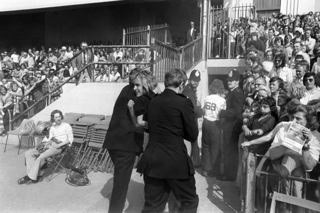 Two policemen remove a football supporter from Highbury, where rival fans clashed as Arsenal played Manchester United. archive-pa163264-4 Date: 25/08/1973