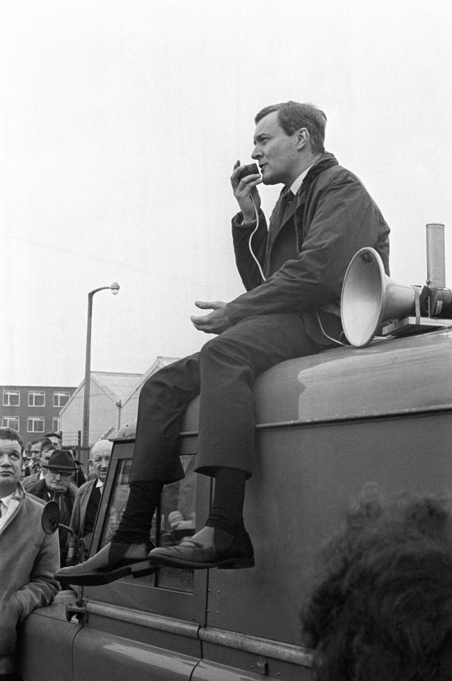 "Seated on the roof of a van, Mr. Anthony Wedgwood Benn, the Minister of Technology, uses a loud hailer to address a factory-gate meeting at Rolls Royce Ltd. workers during his visit to bristol to see work in progress on the Anglo-French Concorde project. Speaking to the Rolls Royce workers as they left for their lunch break, the Minister said that ""if all goes well and the options taken out are converted into firm orders and world airliners make their orders firm, we shall see not only firm production of the production Concorde but a considerable gain in orders for us and for France."" 138048-4 Date: 24/01/1969"