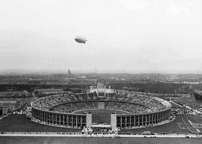 The German airship Hindenburg flies over the Olympic Stadium, outside Berlin, on August 1, 1936, during the opening ceremony of the Olympic Games.